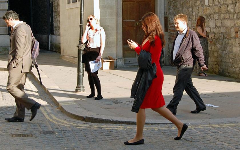 passants qui marchent avec leurs smartphones en main